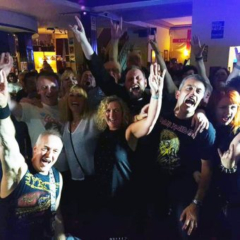 The crowd at the Talbot, Burnley, cheering and waving their arms.