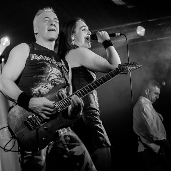 Ann singing, standing next to Neil who's playing guitar. Black and white.