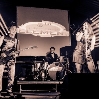 The band playing together on stage, with bright lights fanning out from behind them. Sepia.