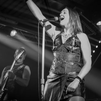 Ann singing on her mic in its stand, right hand raised. Black and white.