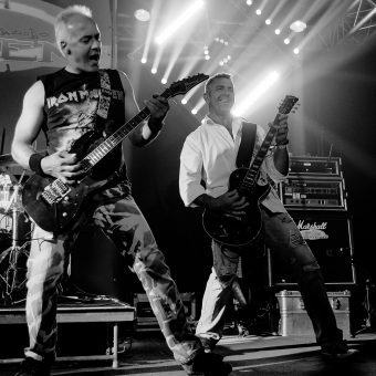 Neil and Alan playing guitar, smiling and singing. Black and white.