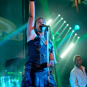 Ann singing on her mic, right hand pointing straight into the air.