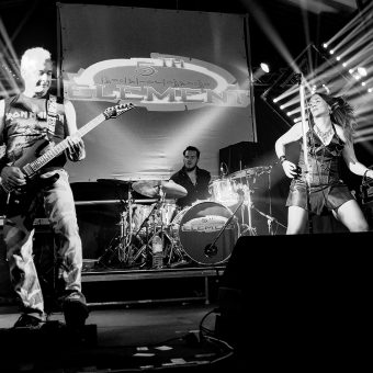 The band playing on stage together, Ann playing air guitar. Black and white.