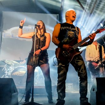Ann singing on her mic, right hand raised. Neil standing next to her, playing and singing.