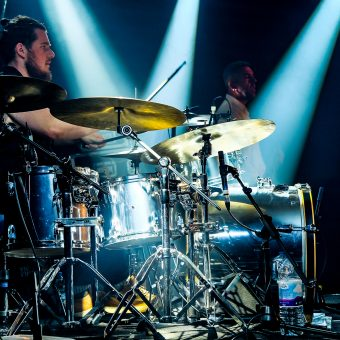 Aaron playing drums, side on.