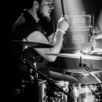 Side on close up of Aaron playing drums, stick raised in his right hand. Black and white.