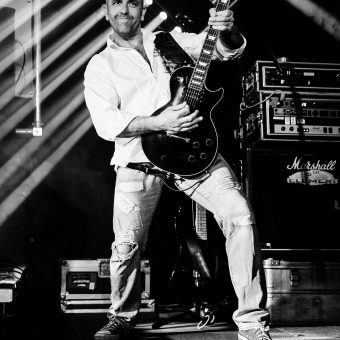 Alan playing guitar, holding it up and smiling. Black and white.