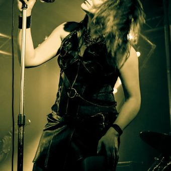 Ann holding her mic in its stand, tossing her hair. Sepia.