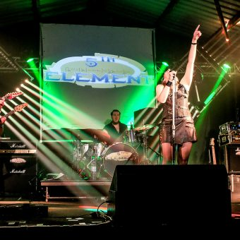 The band playing together on stage. Ann raising her left hand in the air, head thrown back.