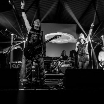 The band on stage, throwing the horns! Black and white.