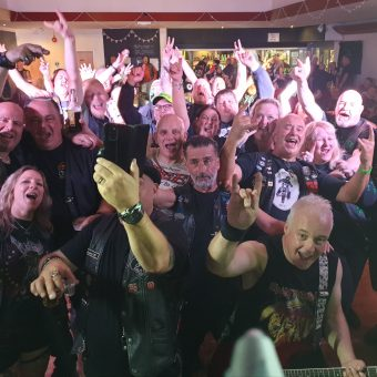 A crowd of bikers, cheering, smiling and waving their arms after the gig. One is taking a selfie. Guitarist Neil has also photo bombed the picture!