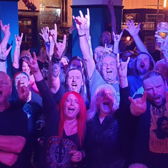 A crowd of pub goers cheering, smiling and waving their arms at the end of the gig.