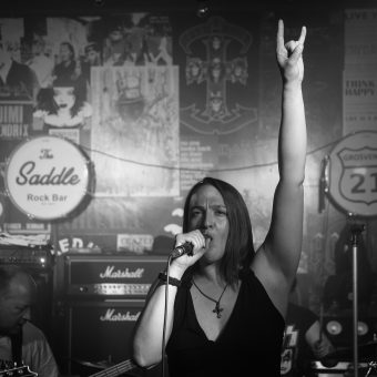 Ann singing and raising the horns, black and white.