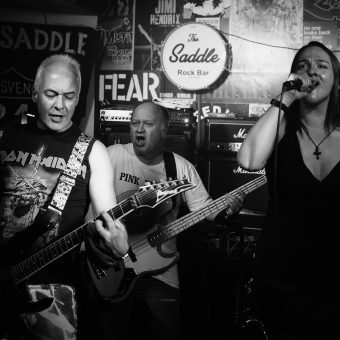 Neil, Pete, Ann and Aaron playing on stage, black and white.