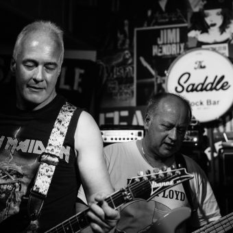 Neil and Pete playing guitar, black and white.