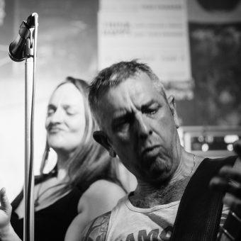 Alan playing guitar, Ann playing air guitar behind, black and white.